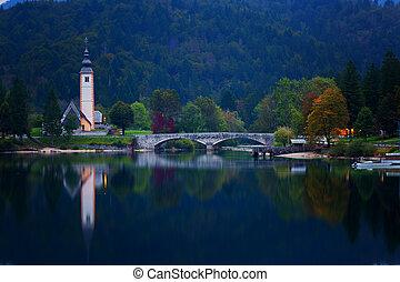 Night view of the stone bridge and the Church of St. John the Baptist at Lake Bohinj (Bohinjsko jezero), Slovenia