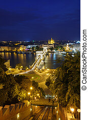 Night view of the Szechenyi Chain Bridge over Danube River and church St. Stephen's Basilica in Budapest