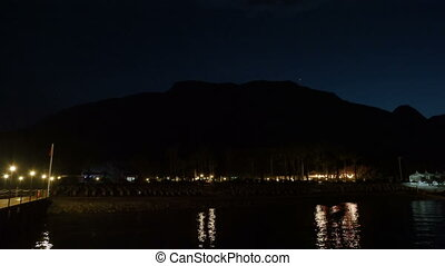 Night view on beach with sun loungers, mountains and stars.