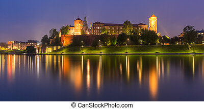 Panorama of Wawel Castle on Wawel Hill with reflection in the river at night as seen from the Vistula, Krakow, Poland