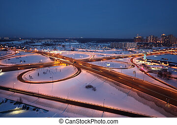 night winter cityscape with big interchange and lighting columns