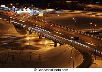 night winter cityscape with big interchange, lighting columns and bridge