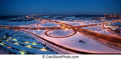 night winter cityscape with big interchange, lighting columns and garages, panorama