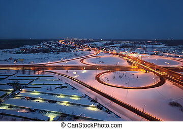 night winter cityscape with big interchange, lighting columns and garages
