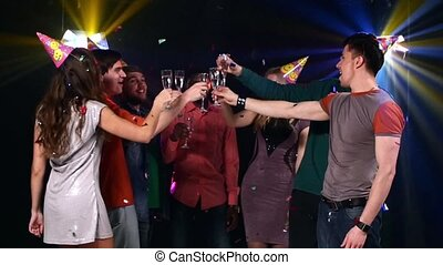 Nightclub : friends party and dancing clink glasses. Slow...