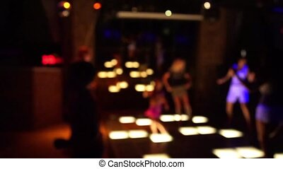 Nightlife and party in holidays, celebration. Blurred background of happy people dancing in night club.