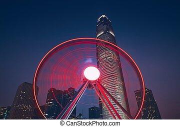 Observation Wheel against urban skyline - Nightlife in Hong...