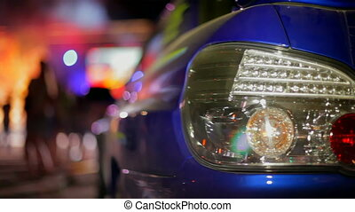 Rear lights car closeup. In the background a disco. The background is blurred. Moving camera. Two frame.