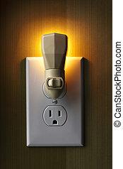 Nightlight aglow - closeup of lit nightlight plugged into...