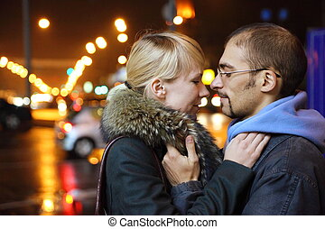 nightly street of coldly fall city. man and woman is embracing.