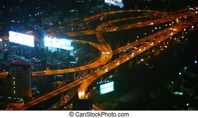 Full HD video - Wide, curving, well-lit ramps of a major highway interchange in downtown Bangkok at night, with light traffic.