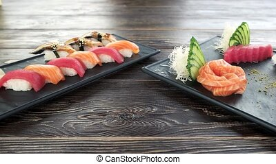 Nigiri and sashimi, wooden table. Delicious food, japanese...