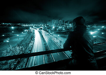 Nigth urban scene with young man, road and tunnel