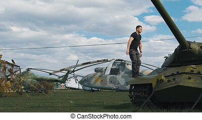 Nimble soldiers at a military base flips. Around battle tanks and helicopters.