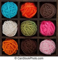 Nine colorful balls of yarn in printers box