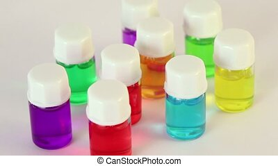 Nine transparent bottles spins with color oil on them