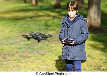 Nine-year-old girl operating toy drone flying by remote control