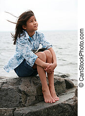 Nine year old girl sitting by lake in summer. Part asian-...
