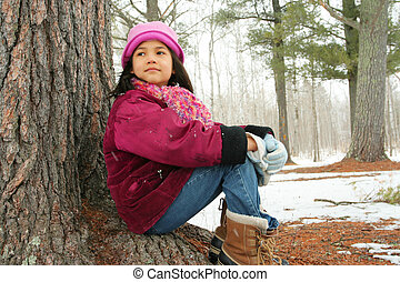 Nine year old girl sitting outdoors in winter - Nine year...