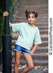 Nine-year-old girl standing on the steps outdoors