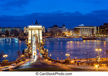 Nineteenth century Chain Bridge (Szechenyi Lanchid) and Budapest cityscape at night. Budapest, Hungary