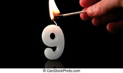 Ninth birthday candle on black background