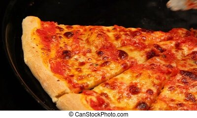 nippers takes pizza slice from frying pan close up