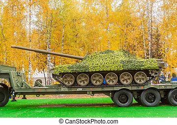 Tank under camouflage network on truck platform