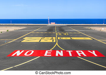 no entry sign at the runway of the airport with ocean in background