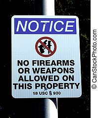 """NO FIREARMS SIGN - A """"no firearms"""" sign against a dark..."""