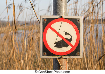 No fishing sign on a post by a river
