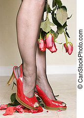 A woman in bright red patent leather shoes crushing roses portraying unforgiveness and anger.