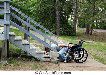 Man in a wheelchair falls down trying to get up stairs