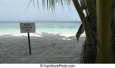 Sign warns of no lifeguard at this white sand, tropical beach paradise on a remote island in the Maldives. 4k video