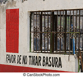 Abandoned building with sign please no trash dumping in spanish