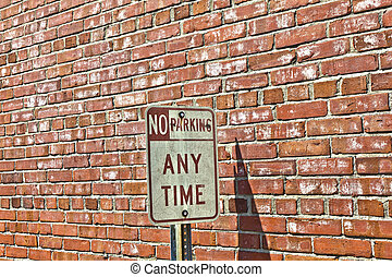 no parking sign in front of brick wall