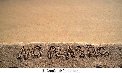 No Plastic text hand written on sandy beach background.