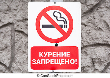 No smoking sign in Russian against a gray stone background