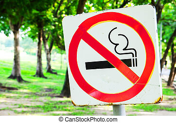 No smoking sign in the park on bright green trees and grass background.
