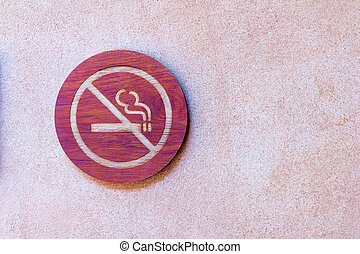 No smoking wooden sign on cement wall