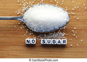 No sugar phrase made from plastic letter cubes placed in a spoon full of sugar