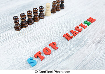 No to racism in colored letters on a gray wooden background