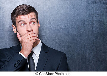 No way! Shocked young man in formalwear covering mouth with...