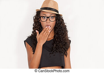 No way! Surprised young African woman in glasses and funky hat covering mouth with hand and looking at camera while standing against white background