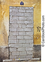 nobody home - Bricked up door and weathered wall of an...
