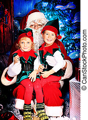 noel and elves - Santa Claus sitting with two little cute ...