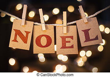The word NOEL printed on clothespin clipped cards in front of defocused glowing lights.