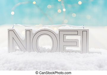 NOEL in Snow with blue and white bokeh background