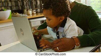 noir, ordinateur portable, vue côté, utilisation, cuisine, père, table, dîner, 4k, fils, jeune