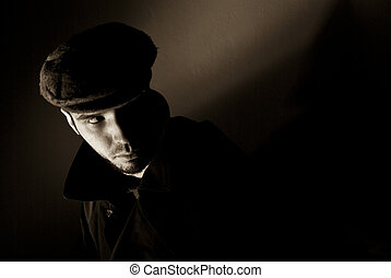 Sepia toned noir portrait of suspicious looking young man. Harsh highlights and shadows.
